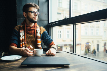 Vertical portrait of friendly bearded male freelancer in glasses dressed in sweater having a break with coffee, dreaming while sitting in loft studio near big window.