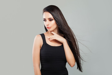 Young Woman Fashion Model with Long Healthy Hair and Natural Makeup on Gray Background