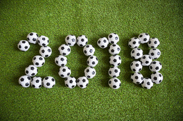 Message for new year 2018 formed from little balls on green football sports pitch