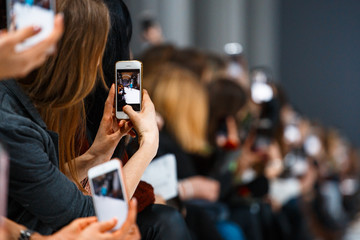 Woman making photo on smatrphone while watching fashion show