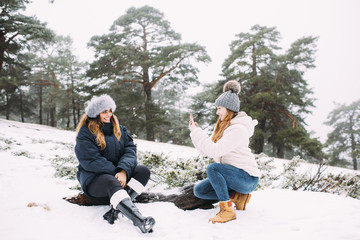 Friends taking photographs in snowy weather