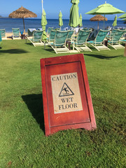 Humorous Caution Wet Floor sign on grass at Hanalei Bay Kauai