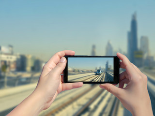 Female's hands take a picture of Dubai monorail and skyscrapers on mobile phone. Picture of subway road and metro train  on downtown city Dubai on smartphone. United Arab Emirates