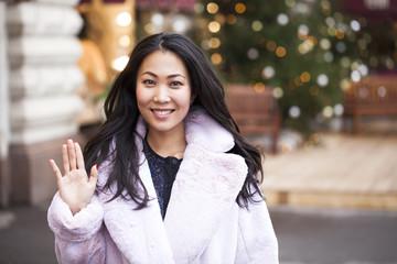 Happy asian woman in winter coat from faux fur
