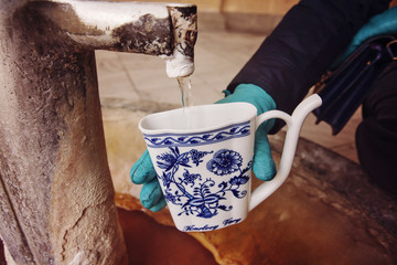 Hand in glove filling a cup with therapeutic mineral water at a natural hot spring in Karlovy Vary during winter time, Czech Republic