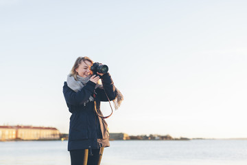 Woman taking photograph by sea