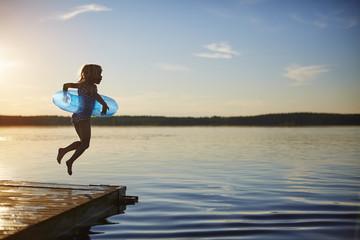 Girl jumping off a pier