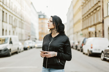 Woman holding a smart phone on a street in Stockholm