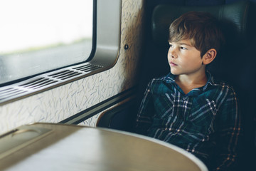 A young boy travelling on a train