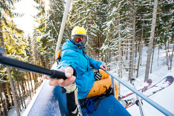 Shot of a skier taking a selfie with a selfie stick while riding ski lift to the top of the mountain at winter sports resort people technology social activity travelling journey trip concept