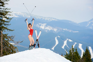 Active woman skier in a red swimsuit, holding poles above head, posing with skis on the top of the mountain at ski resort. Hills and ski slopes on the background. Ski season and winter sports concept