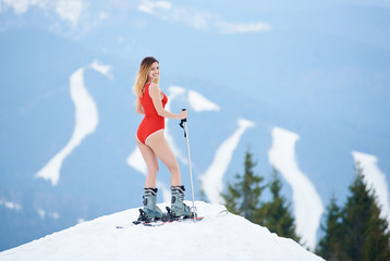 Happy girl skier wearing red swimsuit, smiling to the camera, standing with skis on the top of the slope. Mountains, forests, ski slopes on the background. Ski season and winter sports concept