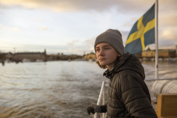 Boy on a boat with the Swedish flag in Stockholm, Sweden