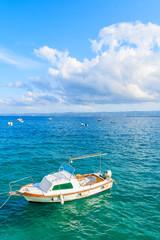 White fishing boat on blue sea and beautiful sunny sky with white clouds in Bol port, Brac island, Croatia