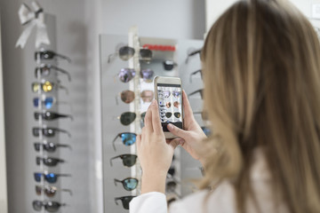 Woman taking picture to glasses in stan for see later at home what model buy or share social networking