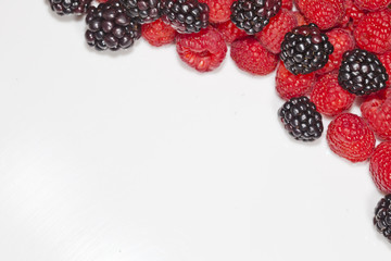 Blackberries and raspberries framed on white with copy space.