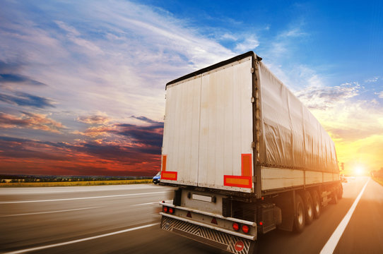 Semi truck with a white trailer driving fast on the countryside road against a night sky with a sunset