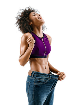 Sporty girl pulling her big jeans and showing weight loss. Photo of african girl on white background. Strength and motivation