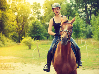 Jockey girl doing horse riding on countryside meadow