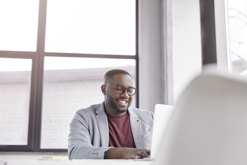 Glad black man manager keyboards on laptop computer, searches information about marketing agency. Positive dark skinned experienced male communicates through online chat, works on creating website
