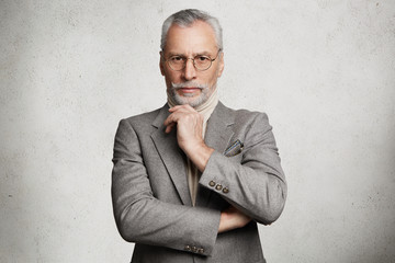 Indoor shot of prosperous experienced elderly wrinkled businessman dressed in grey formal suit,...