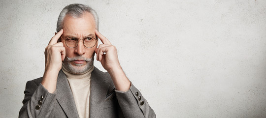 Elderly bearded man dressed in formal clothes, keeps fingers on temples, tries to concentrate and get idea, looks pensively and seriously aside, isolated over white background with copy space