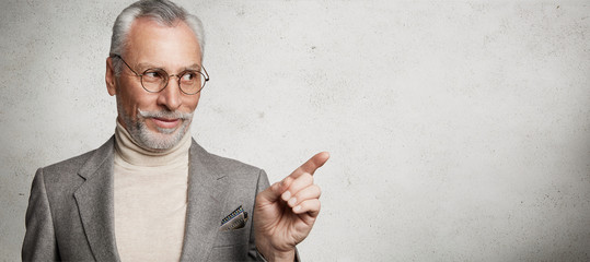 Horizontal shot of pleased grey haired old male dressed in formal suit and round spectacles, rejoices his purchase, indicates with fore finger aside at copy space for your advertising content Wall mural