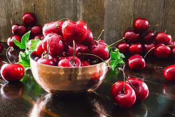 Copper Bowl of Cherries on Dark Table