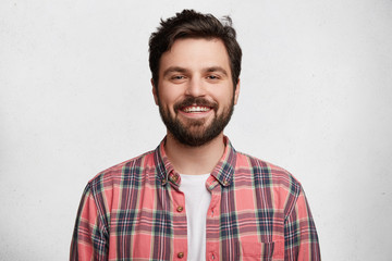Smiling bearded young male model rejoices coming weekends, dressed casually, isolated over white background. Positive pleased student being in good mood after successfully passed exams at college Wall mural