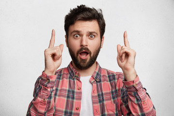 Caucasian bugged eyed male has trendy hairdo, points upwards with fore fingers, isolated over white background, shocked to advertize something. Handsome man with shocked expression. Reaction, attitude