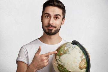 Portrait of serious confident unshaven man with trendy hairstyle, holds globe, chosses destination for travelling with girlfriend, likes to explore new unknown places, isolated over white background
