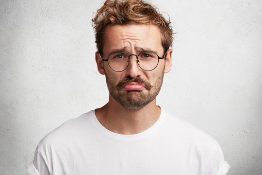 Depressed bearded male model curves lips and looks stressfuly at camera, being not ready to sustain defeat, has regretful expression, feels lonely and bored, isolated over white studio background
