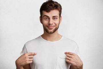 Positive glad blue eyed attractive man with stubble indicates at blank space of t shirt for your advertising text or logo, isolated over white background. People, clothing, design and fashion concept