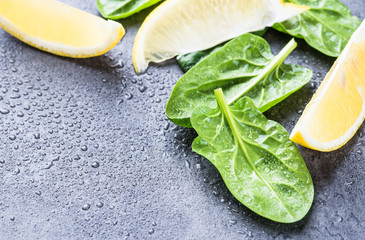 Fresh spinach leaves and slices of lemon fresh ingredients on grey stone background text space.