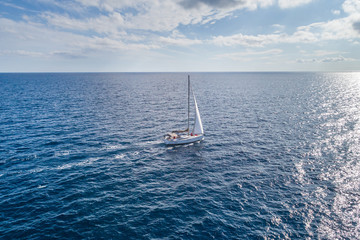 Aerial view on a white yacht under a white sail. Montenegro.