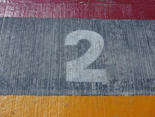 Weiße Zahl 2 auf Betonboden zwischen einem gelben und einem roten Streifen