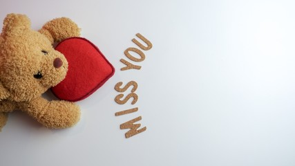 Top view of cute brown teddy bear looking up while holding bright red heart in front of the word miss you on white background leaving copy space on the right side of the photo.