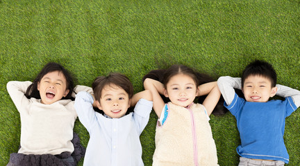 happy boys and girls lying on green grass.