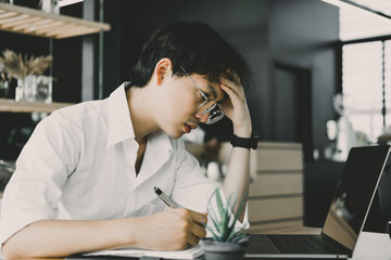 student using computer for learning leasson online at cafe. startup man writing note on notebook at office.  young male entrepreneur feeling tired, frustrated & stressed at workplace.