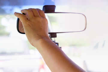 Hands are adjusting the rearview mirror