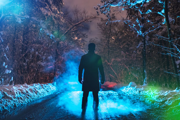 The man stand on a forest road on the smoke background. evening night time