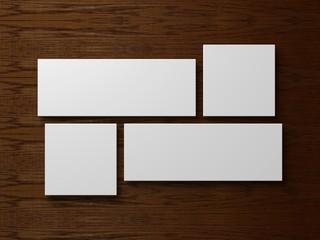 vier leere weiße Leinwände vor einem Holzhintergrund