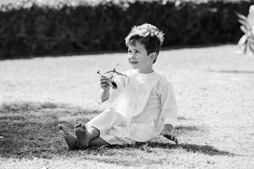 Arabic boy plays with toy helicopter.Black and white.