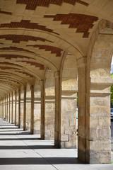 Arcades brique et pierre de la place des Vosges à Paris, France