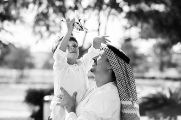 Arabic father and little kid play outdoors.Black and white.
