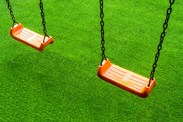 Swing seat on the artificial grass playground