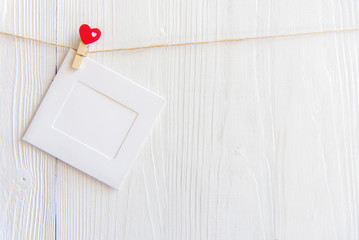 Blank instant photo frame and red  heart hanging on the clothesline. On white old wood background.  Valentine Concept..