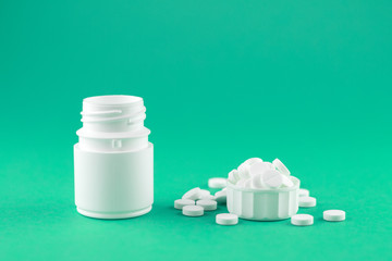 Close up white pill bottle with spilled out pills and capsules in cap on emerald green background with copy space. Focus on foreground, soft bokeh. Pharmacy drugstore concept