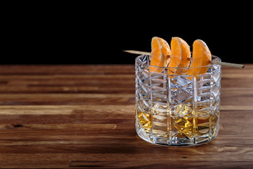 whiskey in a crystal glass with tangerines is on the oak surface of the table