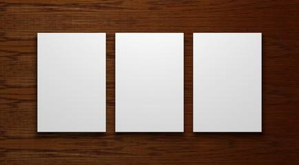 drei leere weiße Bilderrahmen auf einem Holzhintergrund